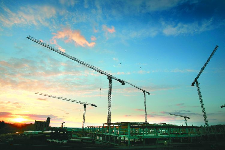 Cranes are left to rotate freely at night to minimize forces if high winds should develop.  03082005  KEITH MYERS/The Kansas City Star Tower crane operator. Construction site. IRS Service Center on Pershing Road across from Union Station. Job site. Kansas City, Missouri. Sunset. CUTLINE On the cover: Cranes are left to rotate freely at night to minimize resistance if high winds should develop. Photo help. Star photographer Keith Myers wasn't allowed to climb the crane. Instead he trained J.E. Dunn employee Blake Barker, who took the pictures from up above. KEITH MYERS/THE KANSAS CITY STAR